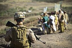 A U.S. Marine watches a group of mock protestors during an e